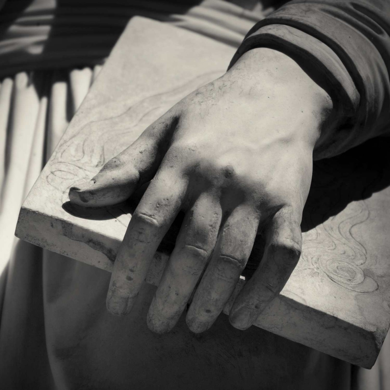 Hand and book detail, statue of Leonardo Da Vinci, Florence, Ita