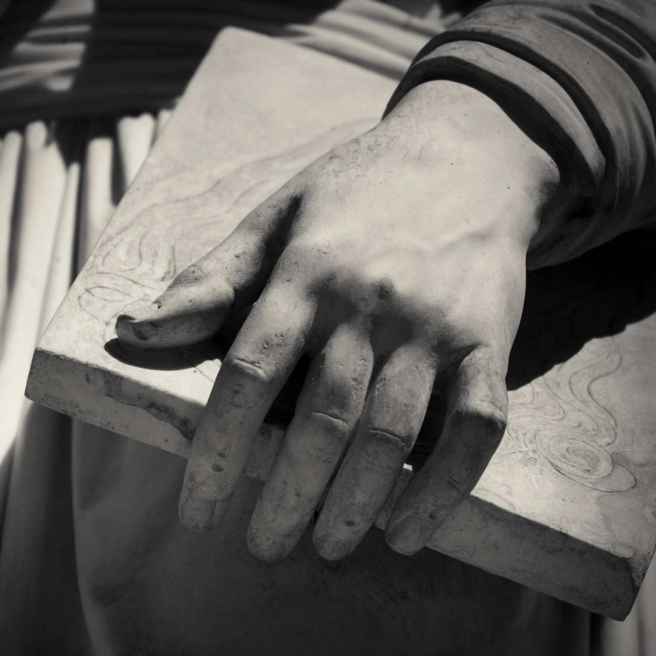 Hand and book detail, statue of Leonardo Da Vinci, Florence, Ita
