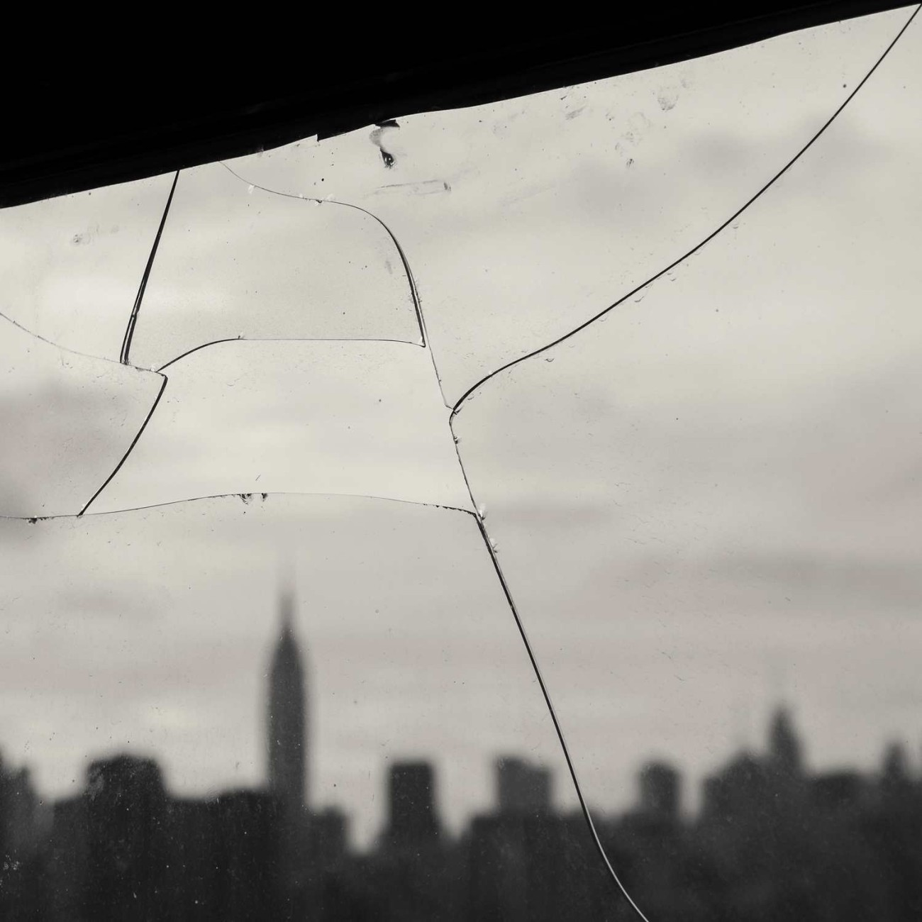 Broken window and Manhattan skyline, NY, 2014
